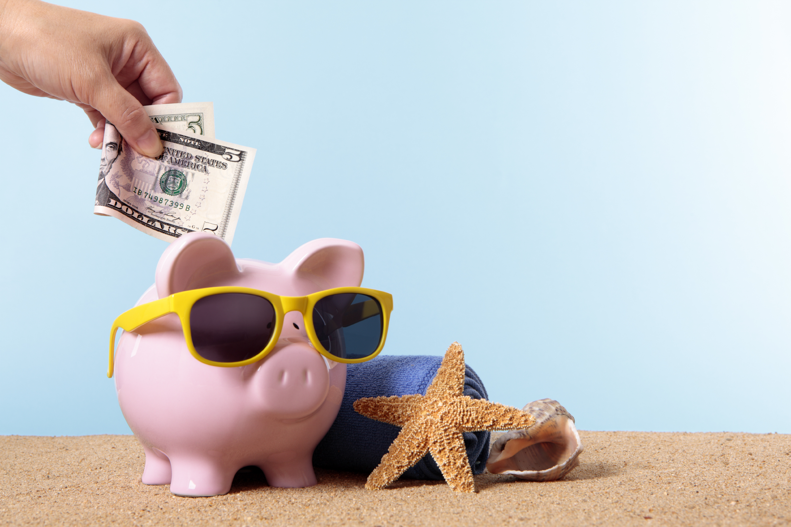 Saving money becomes more of a challenge as summer starts to creep up on us, with pink piggy bank and sunglasses. Studio shot with plain blue background. Sharp focus on the five dollar bill. Space for copy. Warm color and directional lighting are intentional.